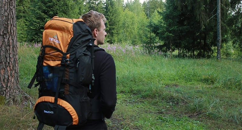 A man wearing the Teton Scout 3400 backpack in a forest