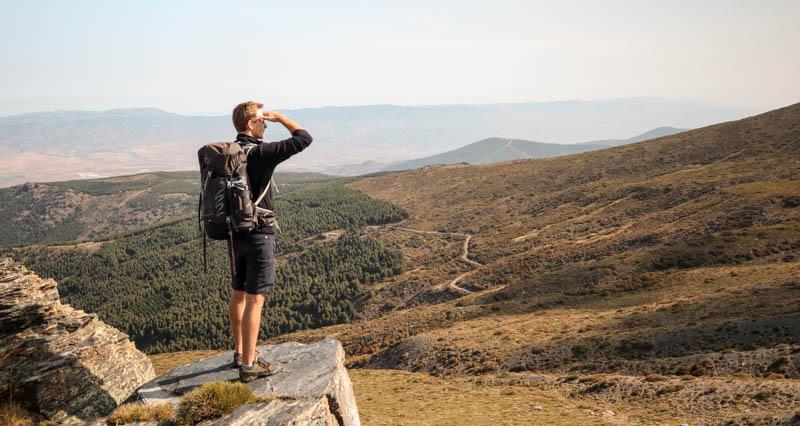 Man wearing osprey talon 44 on a cliff
