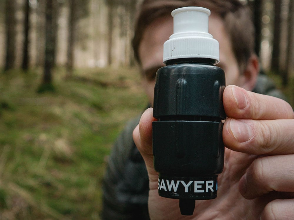 Man holding sawyer micro squeeze water filter