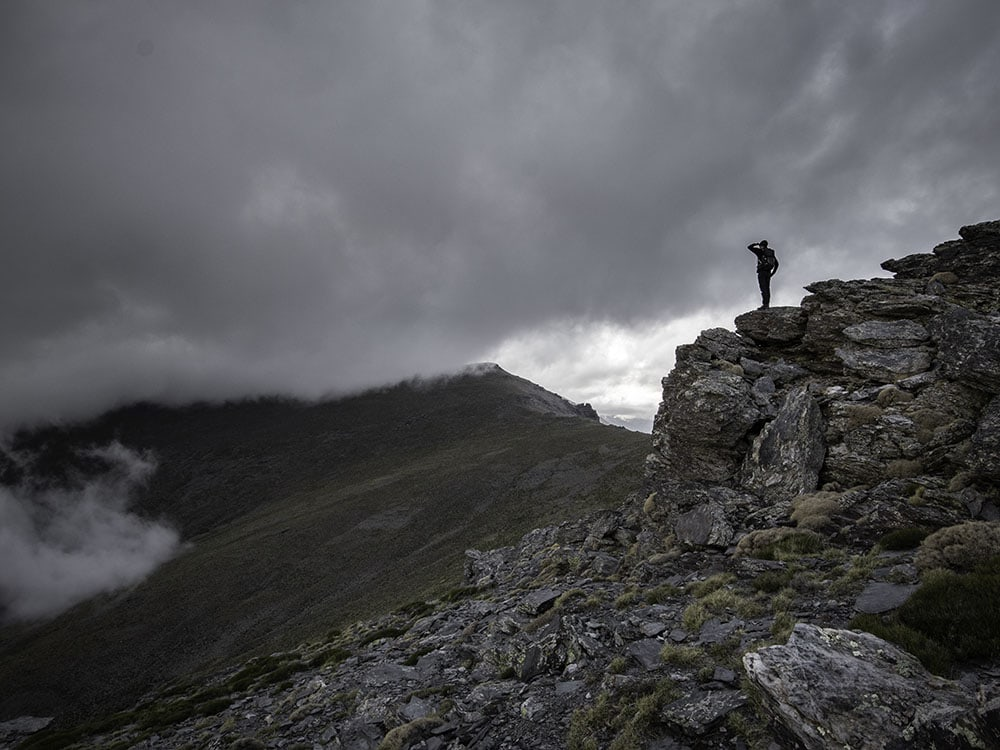 Man standing on a cliff in the mountains in cloudy weather