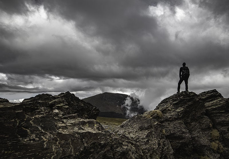 Man standing on rocks in mountains after raining