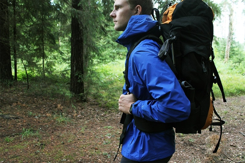 A man standing in a forest with the Teton Sports Scout 3400 internal frame backpack