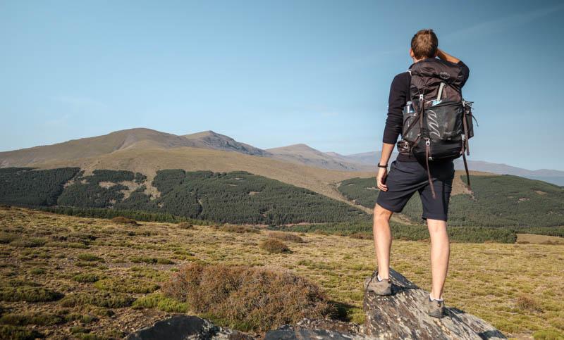 Man wearing Osprey talon 44 backpack in mountains