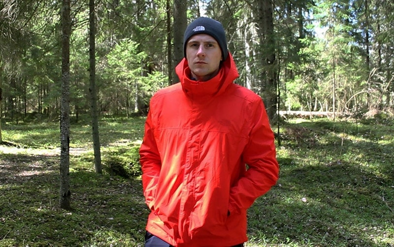 A man wearing a red the North Face Resolve 2 rain jacket