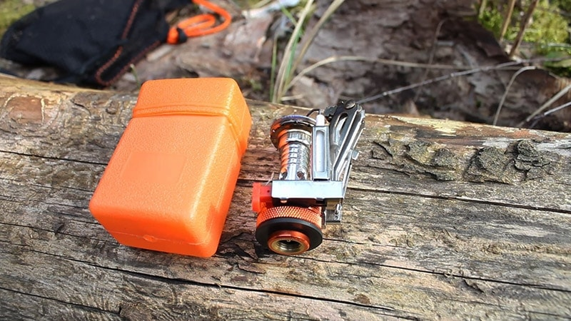 Odoland camping stove laid out on a log